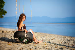 Woman sitting on the swing at paradise beach Stock Images