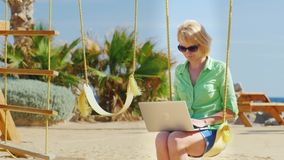 Woman sitting on a swing and uses a laptop.  stock video footage