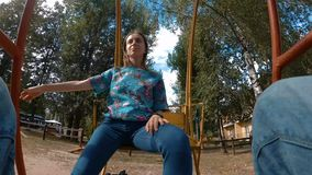 Woman sitting on swing. Looking around and smiling in park - slow motion. Pov - point of view shot. Summer time and leisure concept stock video