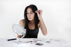 Woman sitting at a table, applying make-up in a sm. All mirror, against white background Stock Images