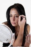 Woman sitting at a table, applying make-up in a sm. All mirror, against white background royalty free stock image