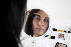 Woman sitting at a table, applying make-up in a sm. All mirror, against white background Royalty Free Stock Photos