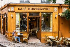 Woman sitting at table in Cafe Montmartre on Montmartre hill. Pa. Paris, France - July 06, 2017: The charming Cafe Montmartre on Montmartre hill. Woman sitting stock image