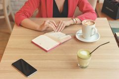 A woman is sitting at a table in a cafe with a spare book. On the table stands a mug of cappuccino, a telephone and a matcha tea. royalty free stock photography