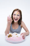 Woman sitting at the table with cake on her face Royalty Free Stock Photos