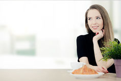 Woman sitting at a table with coffee and croissant Royalty Free Stock Photo