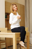 Woman sitting on the table and drinking coffee Royalty Free Stock Images