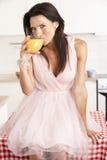 Woman Sitting On Table Drinking Orange Juice Royalty Free Stock Images