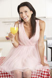 Woman Sitting On Table Drinking Orange Juice Stock Images