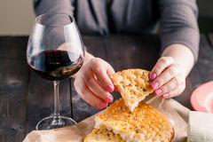 Woman sitting at the table enjoys a bead and a glass of red wine Royalty Free Stock Images
