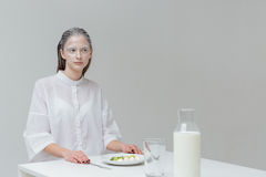 Woman sitting at the table with food Stock Photos