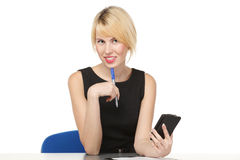 Woman sitting at the table going to make a call Royalty Free Stock Photography