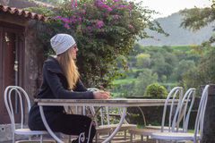 Woman sitting at table in her garden Royalty Free Stock Photo