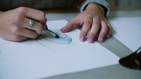 Woman sitting at table, holding pencil and coloring sketch of shoes on paper. Slider right, camera goes by circle. 4K stock video