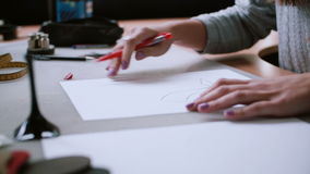 Woman sitting at the table, holding pencil and drawing layout on paper. Erase in sketch. Slider left, side view. 4K stock video footage
