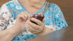 Woman sitting at the table holds a cell phone stock footage