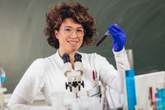 Woman is sitting in lab and holding blood test tube stock photography