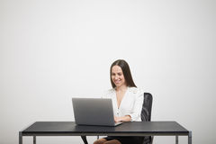 Woman sitting at the table with laptop Stock Photos