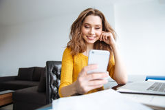 Woman sitting at the table with laptop and using smartphone Stock Photo