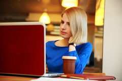 Woman sitting at the table with laptop Royalty Free Stock Photo