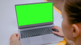 Woman looking at laptop computer with blank green screen in cafe. Woman sitting at table and looking at grey laptop computer device with blank green screen in stock video footage