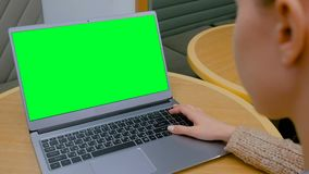 Woman looking at laptop computer with blank green screen in cafe. Woman sitting at table and looking at grey laptop computer device with blank green screen in stock video