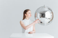Woman sitting at the table with mirror ball. Beauty portrait fo a young woman sitting at the table with mirror ball isolated on a white background Stock Photos