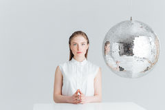 Woman sitting at the table near mirror ball. Attractive woman sitting at the table near mirror ball and looking at camera isolated on a white background Royalty Free Stock Images
