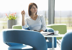 A woman sitting at a table with notes and papers, thinking Royalty Free Stock Photos