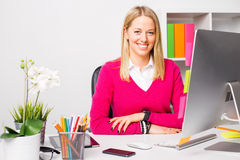 Woman sitting by the table in office Royalty Free Stock Image