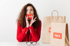 Woman sitting at the table with paper shopping bags. Amazed young sale woman sitting at the table with paper shopping bags isolated over white background Royalty Free Stock Images