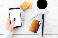 Woman sitting at table and pays the purchase through smartphone royalty free stock images