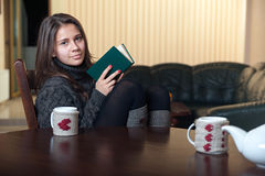 Woman sitting at a table and reading a book. Woman sitting at a table reading a book and drinking tea Royalty Free Stock Photography