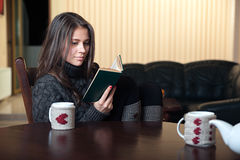 Woman sitting at a table reading interesting book. Woman sitting at the table, thoughtfully reading an interesting book Stock Photos