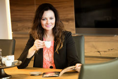 Woman sitting at table and reading magazine Stock Photos