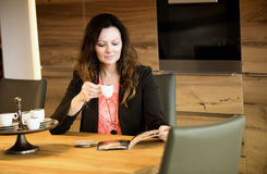 Woman sitting at table reading a magazine Royalty Free Stock Photos