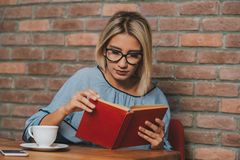 Woman sitting at a table reading a novel book royalty free stock images