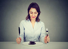 Woman sitting at table smiling looking at her desert chocolate cake. Woman sitting at table happy smiling looking at her desert chocolate cake Royalty Free Stock Image