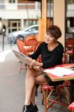 Middle-aged woman discusses new edition of newspaper. Woman sitting at table of street cafe skimmed through new newspaper. Female with short haircut dressed in Royalty Free Stock Images