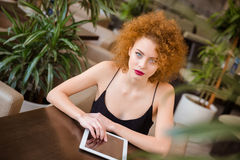 Woman sitting at the table with tablet computer Royalty Free Stock Photo
