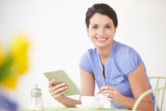 Woman Sitting At Table Using Digital Tablet Royalty Free Stock Photos