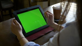 Woman sitting at a table using green screen tablet pc and making zoom in and out gestures in cafe stock video
