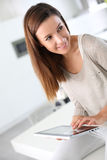 Woman sitting on table and websurfing with tablet Royalty Free Stock Photos