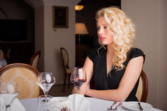 Woman sitting by the table with wine glass Stock Images
