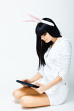 Woman sitting with tablet pc. Serious young woman sitting with tablet pc Stock Photo