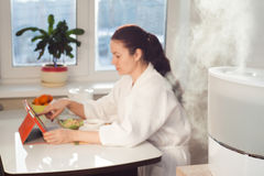 Woman sitting with tablet PC on the background of humidifier Stock Photography