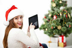 Woman sitting with tablet PC over Christmas tree Stock Image