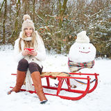 Woman sitting with tea in winter on sled Royalty Free Stock Images
