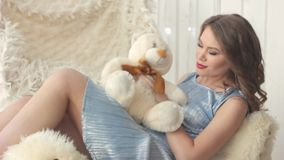 Woman sitting with a Teddy bear. Girl in blue dress lying with a Teddy bear stock video