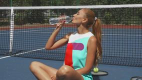 Tennis girl drinring water while relaxing on court stock image